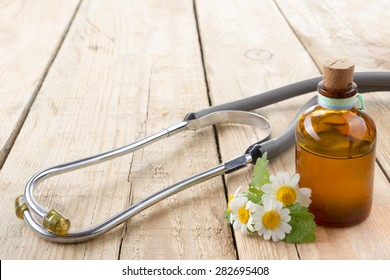 Fresh herb and stethoscope on wooden table. Alternative medicine concept.