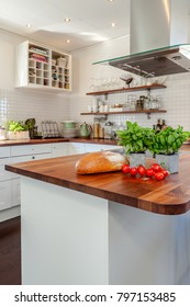 fresh herbs, bread and tomatoes on the wooden counter top
