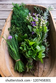 Fresh herbs from garden in wooden basket: chives, mint, thyme, rosemary, dill, sage with edible purple flowers