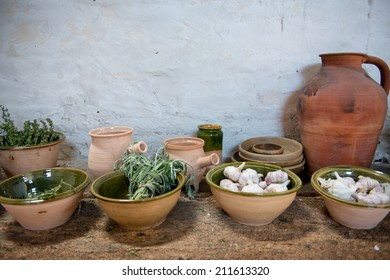 Fresh herbs and garlic displayed in earthenware bowls on an old rustic kitchen counter ready to be used as seasoning and flavoring in cooking