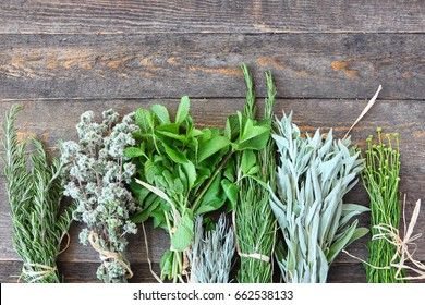 Fresh herbs and spices on the rough wooden background. Natural plants and spices for flavoring food, preparing green tea and medical treatments
