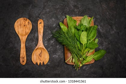 Fresh herbs – spinach, sorrel, dill on wooden plate with wooden salad fork and spoon on black background . Vegan, diet and clean eating concept.