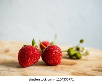 Fresh home grown strawberries on a rustic wooden board
