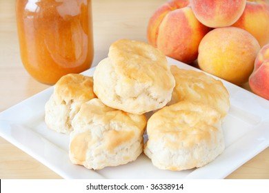Fresh home made biscuits stacked on a white plate with home made peach preserves in the background along with fresh peaches.
