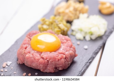 Fresh home made tartare beef steak with egg on black slate plate