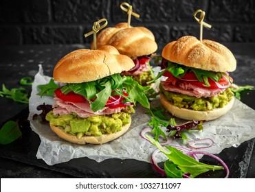 Fresh home sandwich with avocado guacamole, tomatoes, arugula, red onion and ham.