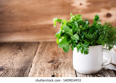 Fresh homegrown organic mint, dill, parsley, cilantro. culinary and aromatic herbs plant in white rural mug on wooden table, home gardening, close up, selective focus