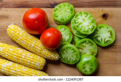 Fresh homegrown organic vegetables including corn, tomato and sliced green tomato. Ripe, juicy and delicious produce ready to prepare for a healthy satisfying nutritious meal.