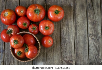 Fresh homegrown red tomatoes on wooden table with copy space. High angle view.