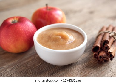 Fresh homemade applesauce (apple puree, mousse, sauce) with cinnamon and apples on wooden table close up