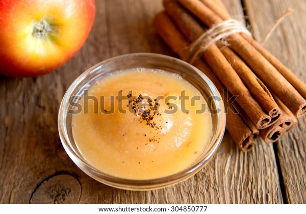 Fresh homemade applesauce (apple puree, mousse, baby food, sauce) with cinnamon (spices), spoon and apples on wooden table close up, horizontal