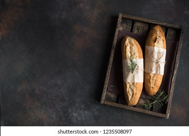 Fresh homemade artisan bread with rosemary on rustic  background, top view, copy space. Sourdough mini baguette bread.