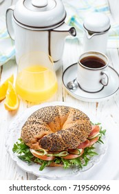 Fresh homemade bagel with ham, lettuce, tomato and cucumber. Breakfast - coffee, orange juice and a delicious sandwich. Selective focus