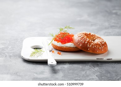 Fresh homemade bagel sandwiches with cream cheese and red caviar, selective focus