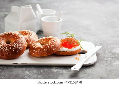 Fresh homemade bagels sandwiches with cream cheese and red caviar on ceramic serving board, selective focus