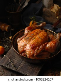 Fresh homemade baked chicken with tangerines on a rustic wooden background.