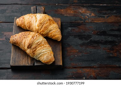 Fresh homemade baked golden brown croissant set, on old dark wooden table background, with copy space for text