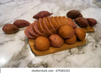 Fresh homemade baked purple japanese sweet potato bread in sliced loaf and buns on wooden cutting board on white marble table top surrounded with real sweet potato