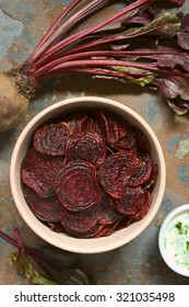 Fresh homemade beetroot chips in bowl, yogurt dip on the side, photographed overhead on slate with natural light (Selective Focus, Focus on the chips on the top)