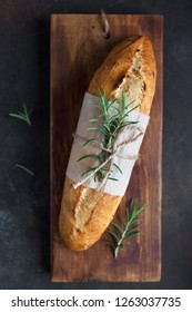 Fresh homemade bread with rosemary on rustic wooden background, top view, copy space. Sourdough mini baguette bread.