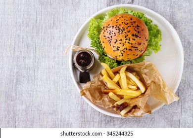 Fresh homemade burger with black sesame seeds in white plate with french fries potatoes, served with ketchup sauce in glass jar over gray wooden surface. Top view