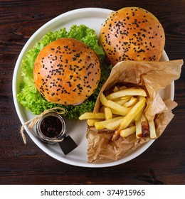 Fresh homemade burger with black sesame seeds in white plate with fried potatoes, served with ketchup sauce in glass jar over dark wooden table. Top view. Square image - Shutterstock ID 374915965