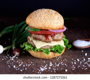 fresh homemade burger with lettuce, cheese, onion and tomato on a rustic wooden board