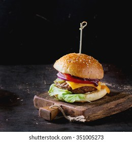 Fresh homemade burger on little wooden cutting board over dark background. Square image with selective focus