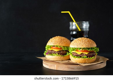 Fresh homemade burgers on sesame buns with succulent beef patties, fresh salad ingredients and glass of coke on little wooden cutting board on dark background with copy space. Horizontal orientation.