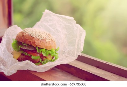 Fresh homemade cheeseburger wrapped in paper, lies on windowsill near an open window