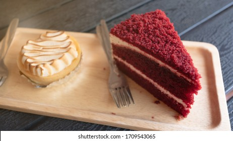 Fresh homemade cheesecake and red velvet cake and forks on wooden plate.