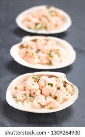 Fresh homemade Chilean salmon ceviche with lemon juice, onion, garlic, salt and cilantro, served on seashells, photographed on slate (Selective Focus, Focus in the middle of the first ceviche)