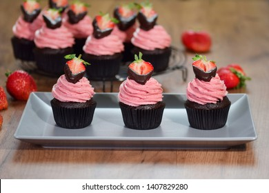 Fresh homemade chocolate cupcakes with buttercream and strawberries.