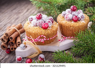 Fresh homemade cranberry muffins holiday in coconut flakes on a wooden background with fir-tree branches. selective Focus