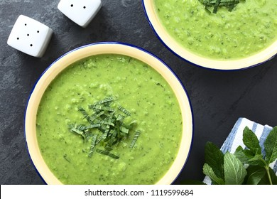 Fresh homemade cream of green pea and mint soup in bowls, garnished with stripes of mint leaves (Selective Focus, Focus on the soup)