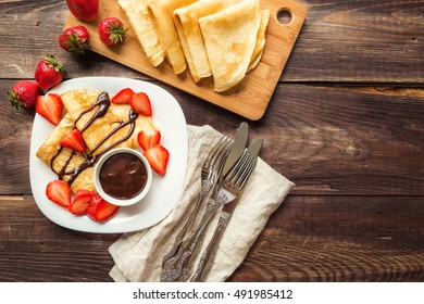 Fresh homemade crepes with strawberries and chocolate sauce on rustic wooden background. Top view.