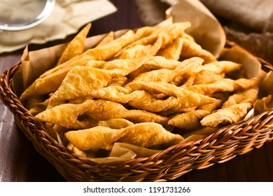 Fresh homemade crispy deep-fried angel wing or bowtie cookies in basket, traditional biscuits in many European countries (Selective Focus, Focus in the middle of the image)