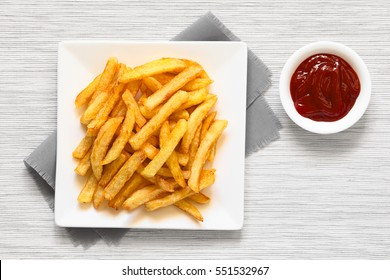 Fresh homemade crispy French fries on plate with a small bowl of ketchup on the side, photographed overhead with natural light