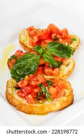 Fresh homemade crispy Italian appetizer called Bruschetta topped with tomato, garlic and basil