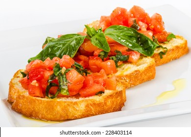 Fresh homemade crispy Italian appetizer called Bruschetta topped with tomato, garlic and basil. Selective focus