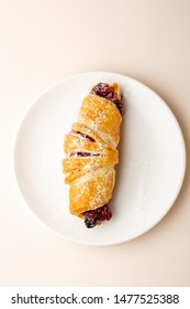 Fresh homemade croissant with cherry on plate