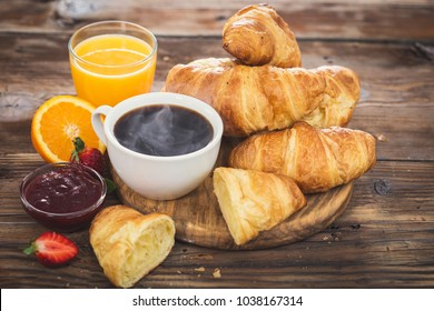 Fresh homemade croissants with black coffe and orange juice