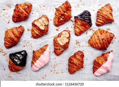 Fresh homemade croissants with chocolate, caramel, strawberry and various toppings. Top view. French bakery concept.