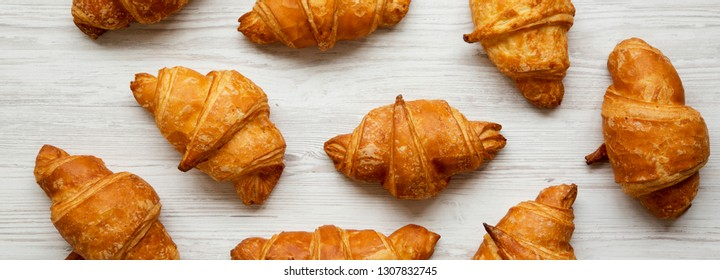 Fresh homemade croissants on white wooden table, top view. From above, overhead.
