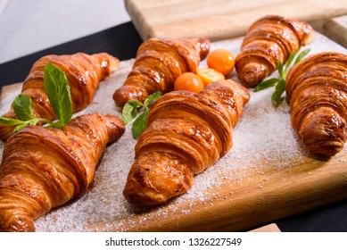 fresh homemade croissants with sugar powder on wood surface