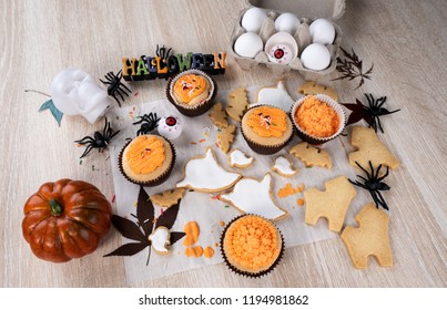 Fresh homemade decorating halloween dessert with ghost, creeping spider, bat, haunted castle and horrifying eyeball on wooden background, copy space