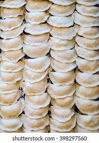 Fresh homemade delicious dumplings (varenyky) are modeled ready for cooking. Top view, background texture.
