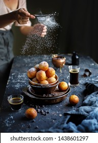 Fresh homemade donuts on the black dark rustic background. Breakfast time with coffee splash. Woman pours suger powder on  donuts