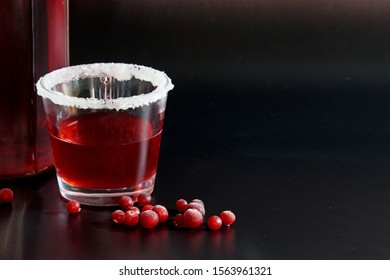 Fresh homemade drink cranberry compote in a glass glass, on a dark background. A handful of berries scattered in front of the glass in the foreground. Place for inscriptions. Copy space.