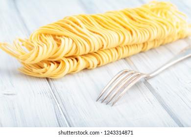 Fresh homemade egg noodles. Italian pasta with fork.